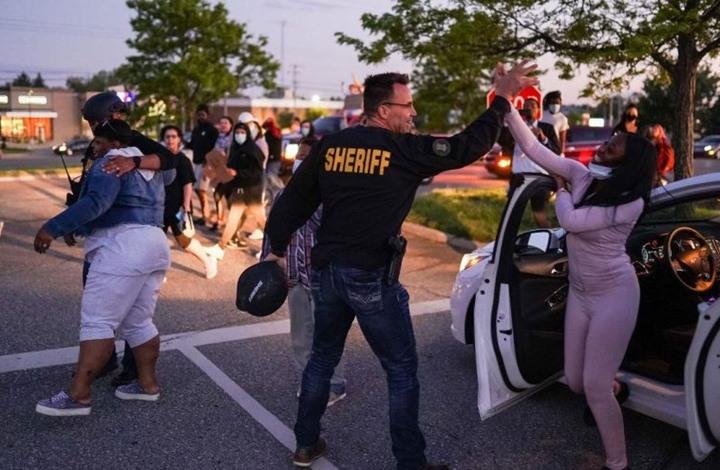 شرطي أمريكي يترك مكافحة الشغب وينضم للمتظاهرين (شاهد)