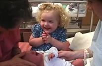 دهشة طفلة صغيرة عند رؤية شقيقها المولود للتو (شاهد)