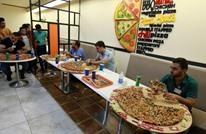 عراقي يأكل بيتزا تكفي 12 شخصا بمسابقة في بغداد