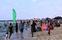 الغزيون يهربون من حر الصيف إلى شاطئ البحر (صور)